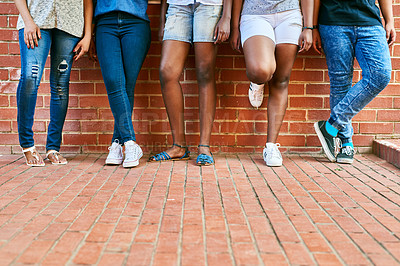 Buy stock photo Cropped shot of a group of unrecognizable university students leaning against a wall on campus