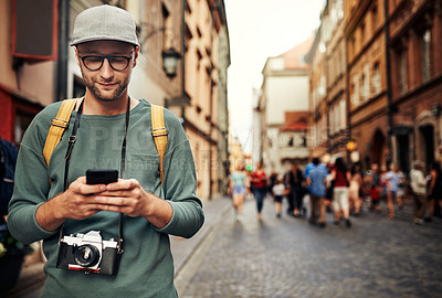 Buy stock photo Shot of a young man using his cellphone while exploring a foreign city