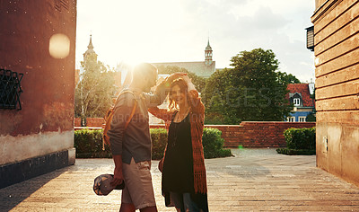 Buy stock photo Shot of a loving young couple dancing in the street while exploring a foreign city