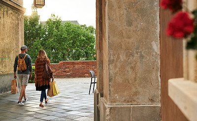 Buy stock photo Shot of a young couple carrying shopping bags while exploring a foreign city