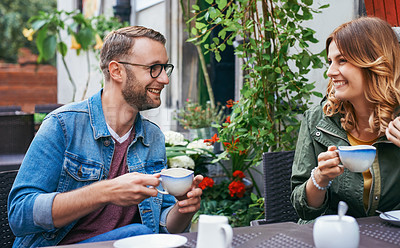 Buy stock photo Shot of a young couple on a coffee date at a sidewalk cafe