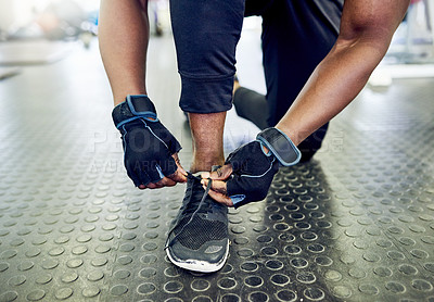 Buy stock photo Cropped shot of an unrecognizable male athlete tying his laces in the gym