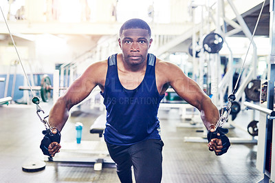 Buy stock photo Cropped portrait of a handsome young athletic man working out on a cable cross machine in the gym