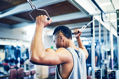 Buy stock photo Rearview shot of a handsome young athletic man working out on a cable cross machine in the gym