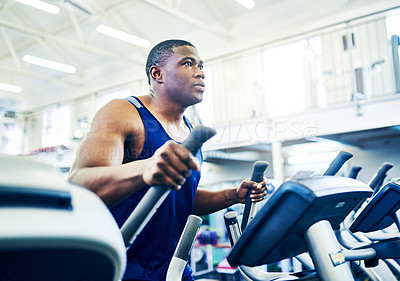 Buy stock photo Cropped shot of a handsome young athletic man working out on an elliptical machine in the gym