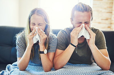 Buy stock photo Shot of a young man and woman blowing their noses with tissue at home