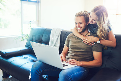 Buy stock photo Shot of a young woman hugging her husband while he uses a laptop on the sofa
