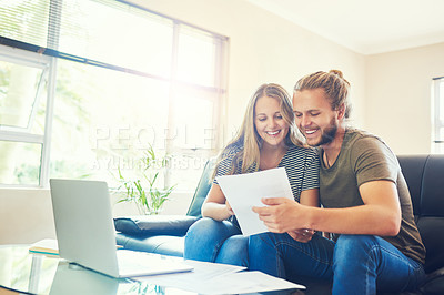 Buy stock photo Shot of a young couple going through paperwork at home