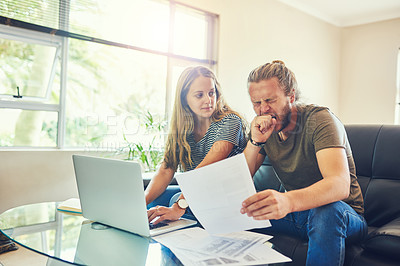 Buy stock photo Shot of a young man yawning while going through paperwork with his wife at home