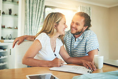 Buy stock photo Shot of a young couple signing a document together at home