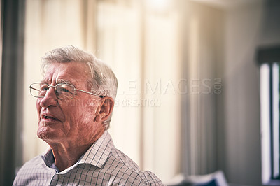 Buy stock photo Cropped shot of a handsome senior man looking thoughtful while standing in his home alone