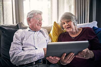 Buy stock photo Cropped shot of an affectionate senior couple using a tablet in their retirement home