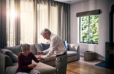 Buy stock photo Cropped shot of a senior man helping his wife with her medication in their retirement home