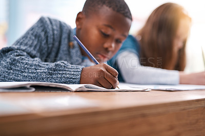 Buy stock photo Cropped shot of two elementary school kids doing school work inside of the class during the day