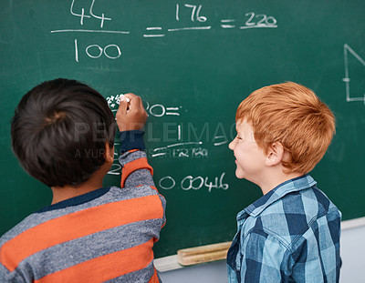 Buy stock photo Cropped shot of two focussed young elementary school kids writing answers to math questions on a green chalkboard in the classroom