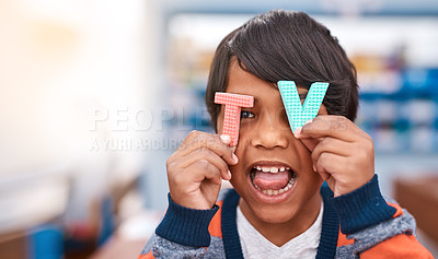 Buy stock photo Cropped shot of a cheerful elementary school kid holding the letters T and V in front of his eyes inside of the classroom