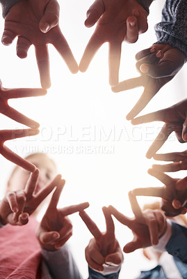 Buy stock photo Low angle shot of a group of cheerful elementary school kids forming a huddle with their hands and showing a hand sign