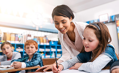 Buy stock photo Shot of a cheerful young female teacher helping a student inside of the class at school