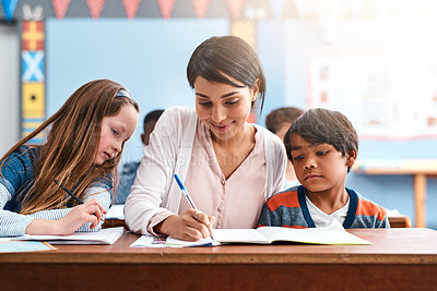 Buy stock photo Shot of a cheerful young female teacher helping her students inside of the class at school