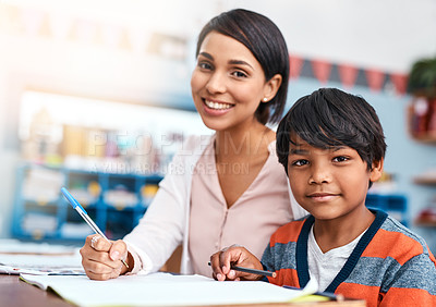 Buy stock photo Portrait of a cheerful young female teacher helping a student inside of the class at school