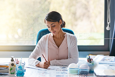 Buy stock photo Cropped shot of a focussed young female teacher marking papers inside of her classroom during the day