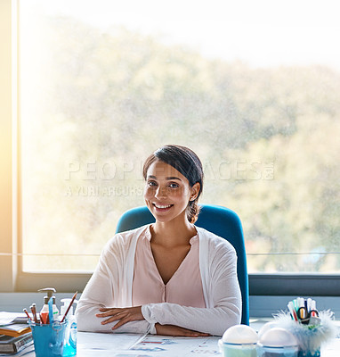 Buy stock photo Portrait shot of a focussed young female teacher marking papers inside of her classroom during the day