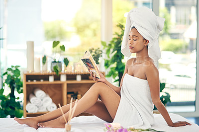 Buy stock photo Shot of an attractive young woman relaxing on a massage table and reading a book at a spa