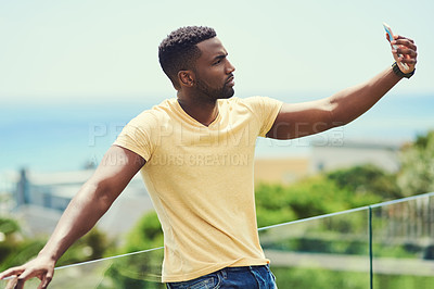 Buy stock photo Shot of a handsome young man taking a selfie with his cellphone while relaxing outdoors on holiday