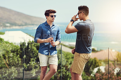 Buy stock photo Shot of two handsome young men having drinks and relaxing outdoors while on holiday