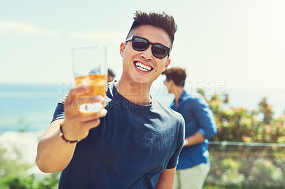 Buy stock photo Portrait of a handsome young man raising up his glass for a toast while relaxing outdoors with his friends