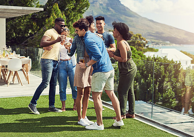 Buy stock photo Shot of a group of friends having drinks and enjoying themselves outdoors while on holiday