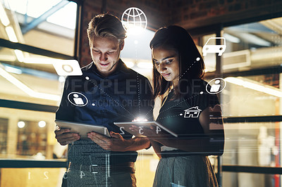 Buy stock photo Shot of two young businesspeople using their digital tablets in their office at work