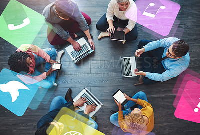 Buy stock photo High angle shot of a group of businesspeople sitting down on the floor and using their digital devices at work