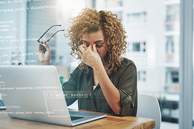 Buy stock photo Shot of a young businesswoman suffering from a headache while using her laptop at work