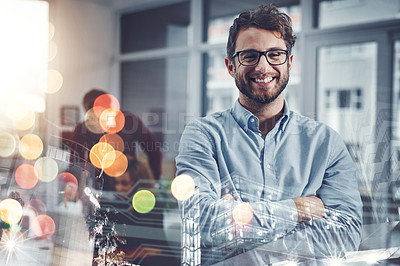 Buy stock photo Portrait of a handsome young businessman posing with his arms folded at work with his colleagues in the background