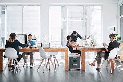 Buy stock photo Shot of a team of businesspeople working together in a modern office