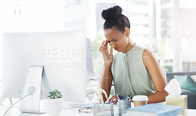 Buy stock photo Shot of an attractive young businesswoman suffering from a headache while working at her desk in a modern office