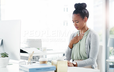 Buy stock photo Shot of an attractive young businesswoman holding her chest in pain while working at the office