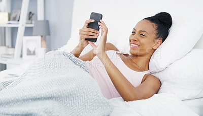 Buy stock photo Shot of an attractive young woman using her cellphone while lying in bed at home