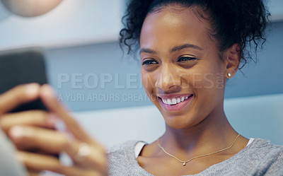 Buy stock photo Shot of an attractive young woman taking selfies with her cellphone while relaxing on her bed at night