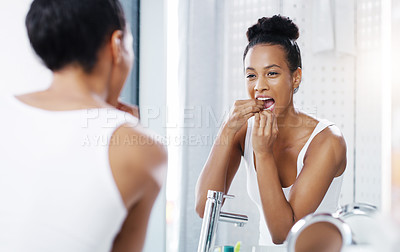 Buy stock photo Shot of an attractive young woman flossing her teeth while looking at the bathroom mirror at home
