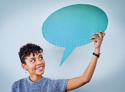 Buy stock photo Shot of an attractive young woman holding up a speech bubble against a blue background