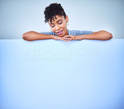 Buy stock photo Shot of an attractive young woman posing against a blue background