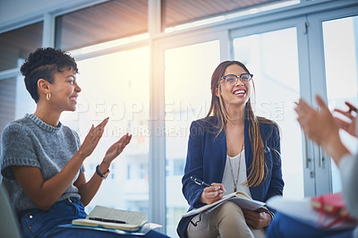 Buy stock photo Shot of a group of young businesswomen giving their colleague a round of applause during a meeting at work