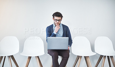 Buy stock photo Cropped shot of a handsome young businessman using a laptop while waiting in line