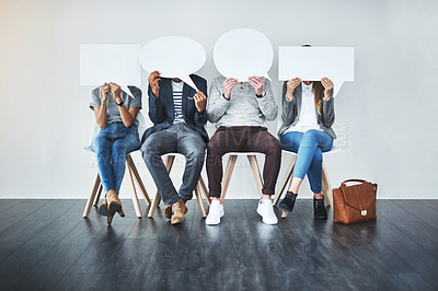 Buy stock photo Cropped shot of a diverse group of unrecognizable businesspeople holding up speech bubbles while they wait in line