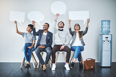 Buy stock photo Full length shot of a diverse group of businesspeople holding up speech bubbles while they wait in line