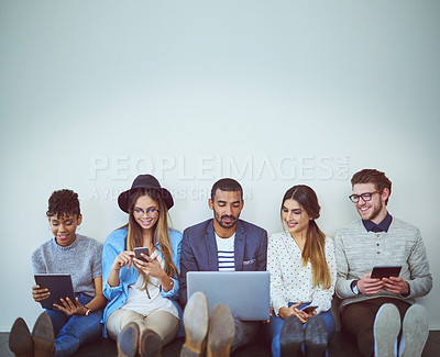 Buy stock photo Studio shot of businesspeople using their devices against a gray background