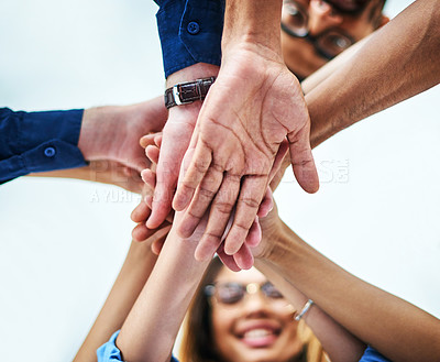 Buy stock photo Low angle shot of colleagues joining their hands together in unity