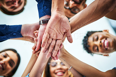 Buy stock photo Low angle shot of  a group of colleagues joining  hands together in unity